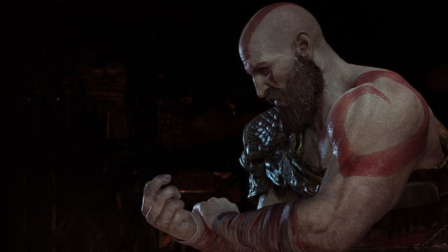 God of War Review | Kratos clenches his fist in a dark room