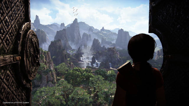Uncharted: The Lost Legacy Chloe looking out over a massive jungle that was behind a previously locked ancient door